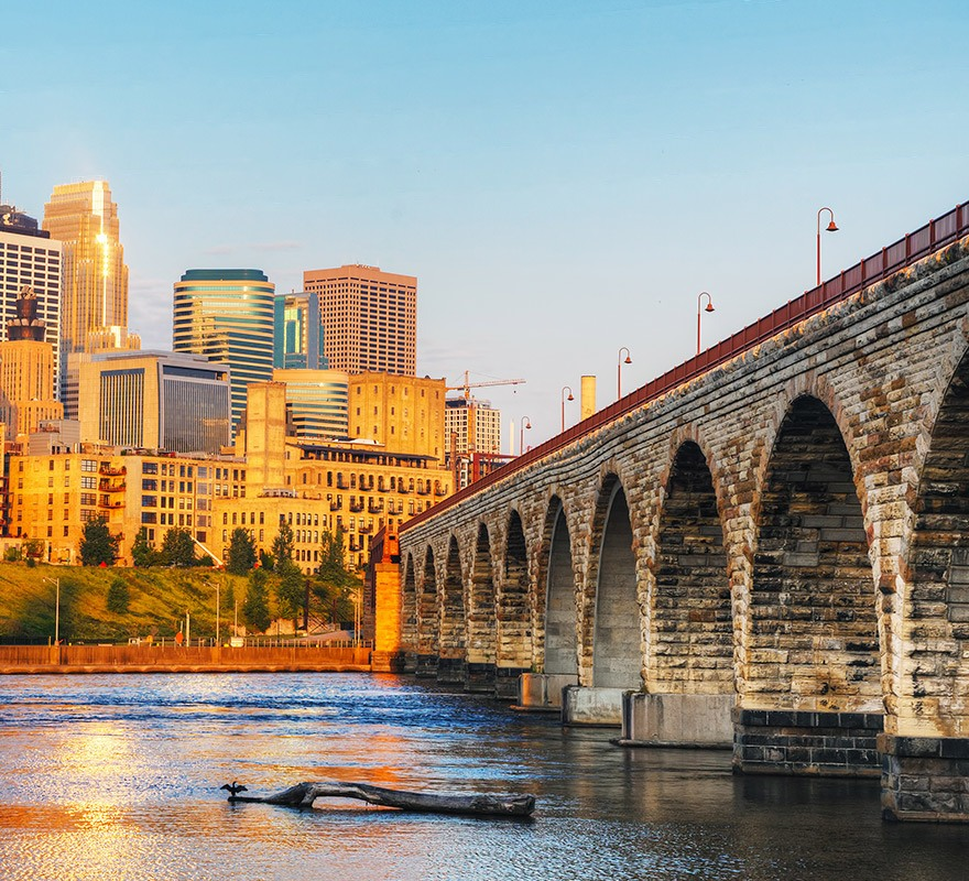 sunset photo of a stone arch bridge on the water with city building in the background